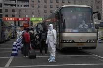Pracovník v ochranném obleku čeká, aby pomohl při nástupu do autobusu cestujícím z Wu-chanu poté, co dorazili vlakem do čínské metropole Pekingu.