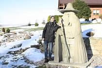 Poutník s otlučenými koleny stojí u sochy Rampušáka.