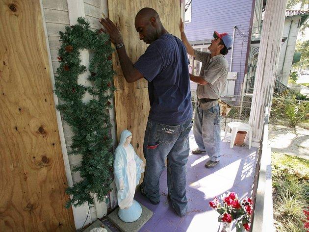 Dělníci zabezpečují okna domu v New Orleans dřevěnými deskami.