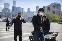 Lidé v rouškách v Pekingu.