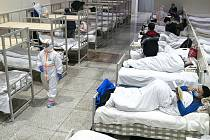 Zdravotníci v ochranných oděvech a pacienti nakažení koronavirem v nemocnici přebudované z výstavnho centra ve Wu-chanu (snímek 5. února 2020)