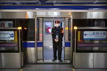 Člen ostrahy s rouškou na obličeji hlídkuje ve vagonu metra v Pekingu