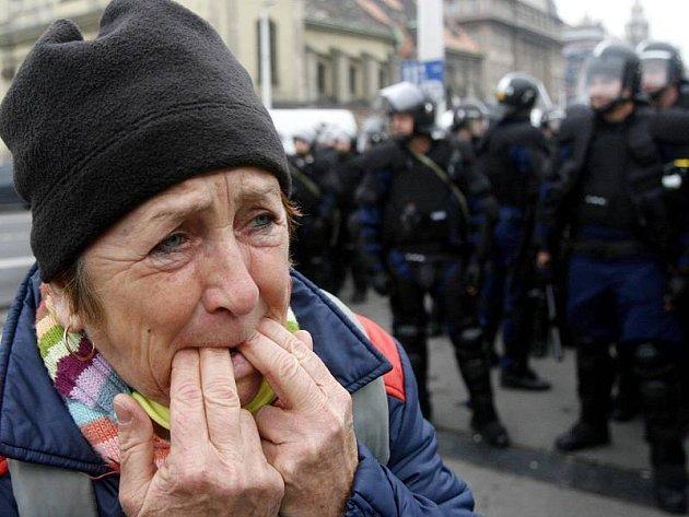 Žena protestuje proti vládě za dohledu policejních jednotek v centru Budapešti.