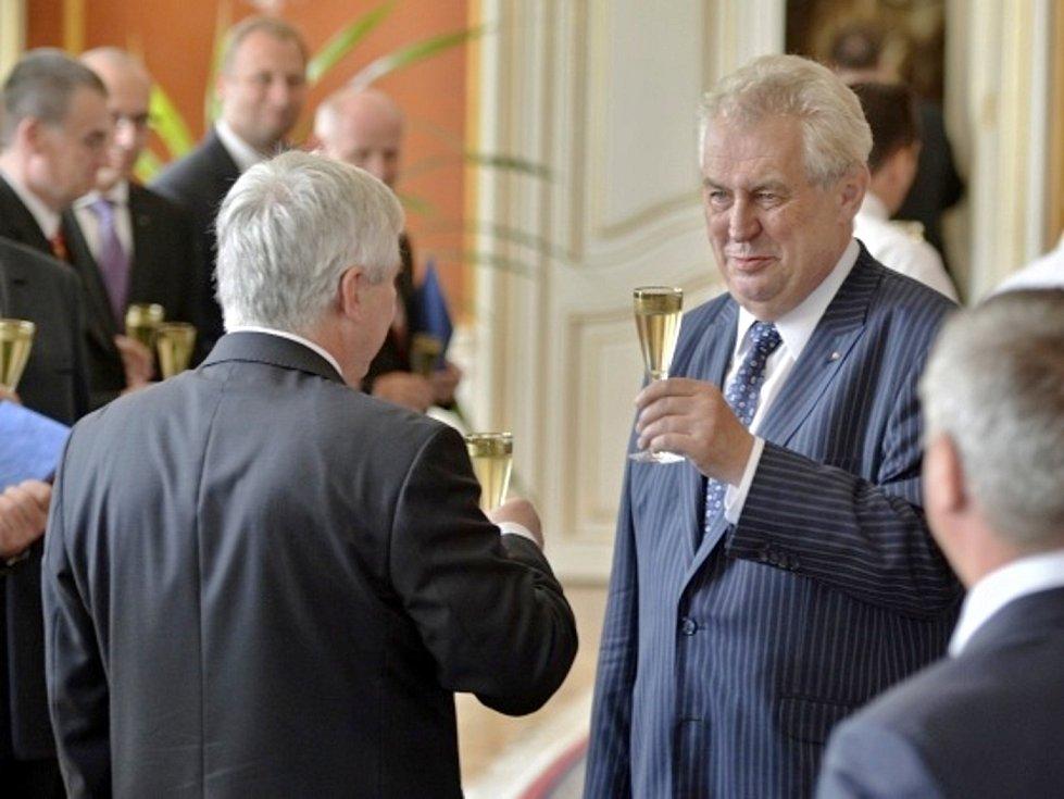 Prezident republiky Miloš Zeman (vpravo) jmenoval 10. července v Praze ministry nové úřednické vlády Jiřího Rusnoka (vlevo zády při přípitku).