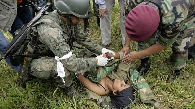 Ekvádorští vojáci poskytují první pomoc zraněné povstalkyni, která zůstala na místě útoku kolumbijské armády.