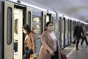 Lidé s rouškami v metru v Moskvě