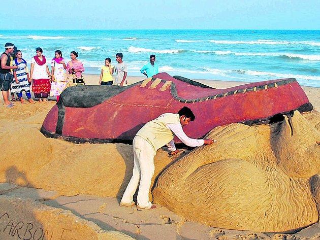 Indický umělec Sudharsan Patnaik upozornil na škody, které působí kožedělný průmysl, svou pískovou sochou ledního medvěda drceného botou.