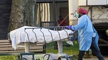 Zdravotník s tělem zemřelého ve zdravotnickém centru v newyorském Brooklynu, 8. dubna 2020