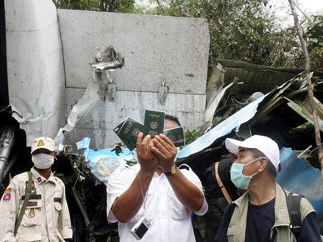 Kambodžský záchranář před troskami letadla ukazuje pasy některých z turistů, kteří zahynuli při leteckém neštěstí.