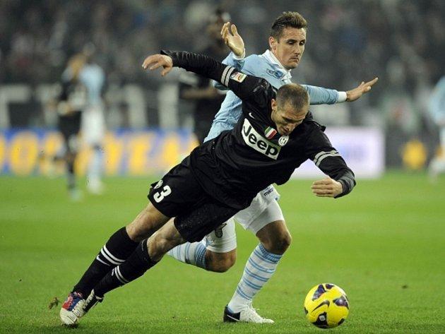 Obránce Juventusu Giorgio Chiellini (vlevo) neustál střet s Miroslavem Klosem z Lazia Řím.