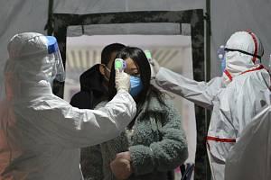 Vládní pracovníci měří teplotu cestujícím na vlakovém nádraží v čínském městě Fu-jang na snímku z 29. ledna 2020
