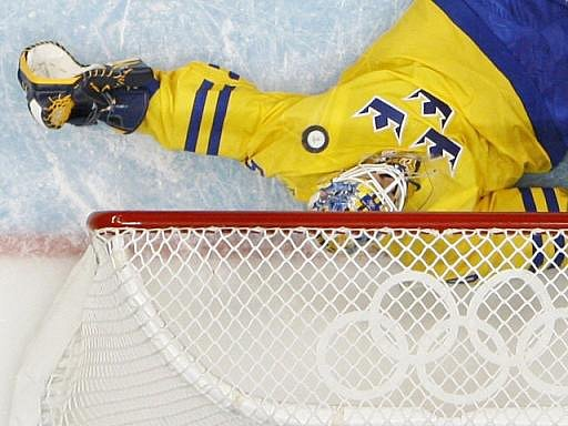 Švédský gólman Jonas Gustavsson proti střele Bělorusa Aleksandra Kulakova.