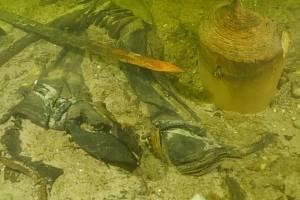 Ostatky středověkého vojáka, jak je i s dochovanými zbraněmi objevili na dně litevského jezera potápěči