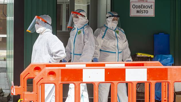 Zdravotníci dezinfikují a odnášejí vybavení odběrného místa k testování lidí s podezřením na přítomnost koronaviru.