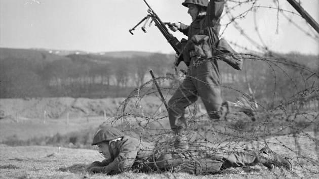 Commandos předvádějí techniku pro překračování ostnatého drátu během výcviku ve Skotsku