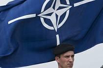 Voják stojí pod vlajkou se znakem NATO - ilustrační foto