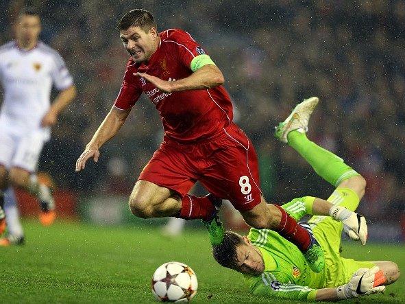 Basilejský brankář Tomáš Vaclík se vrhá pod nohy pronikajícího Stevena Gerrarda z Liverpoolu.