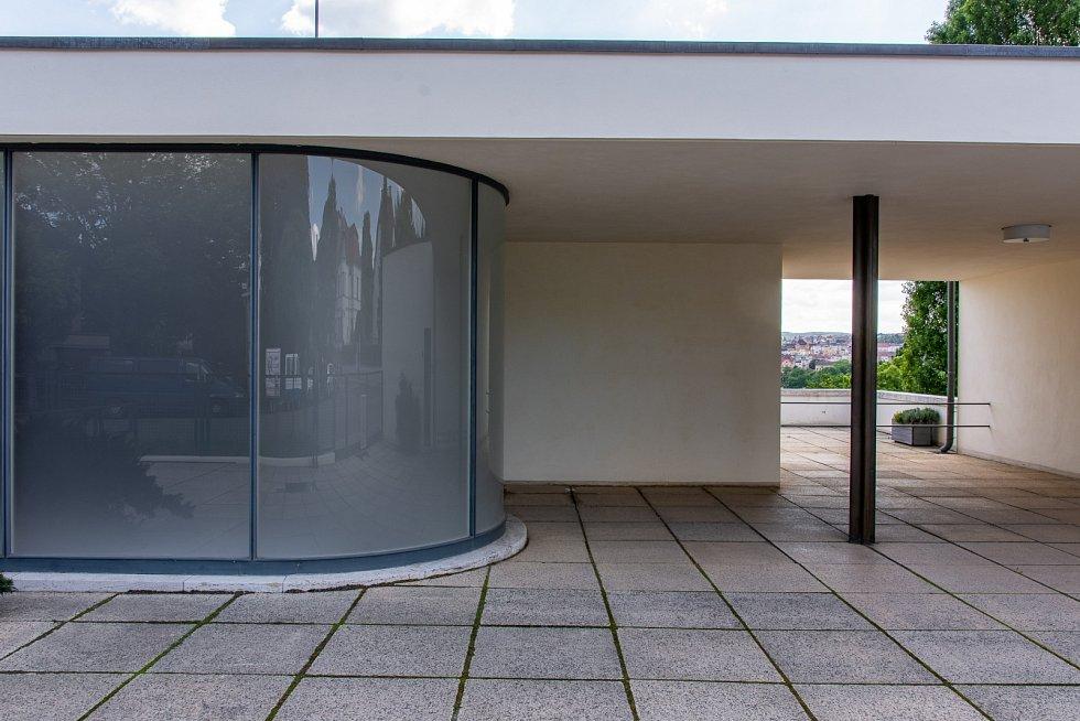 Uliční průčelí tvoří jen třetí obytné podlaží s elegantně zapuštěnými vstupními dveřmi a garáž s bytem řidiče.