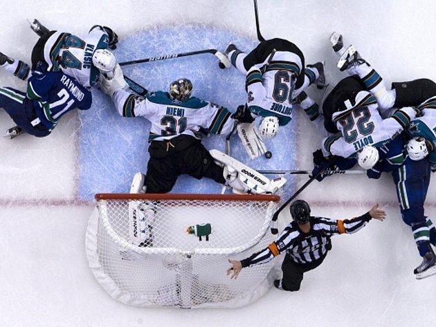 Gólman San Jose Antti Niemi čelí útoku hokejistů Vancouveru.