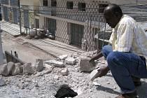 Muž v Mogadišu si prohlíží otvor po výbuchu minometného granátu. Boje mezi islamisty a vládními somálskými jednotakmi podporovanými Etiopií by však měly snad načas skončit.