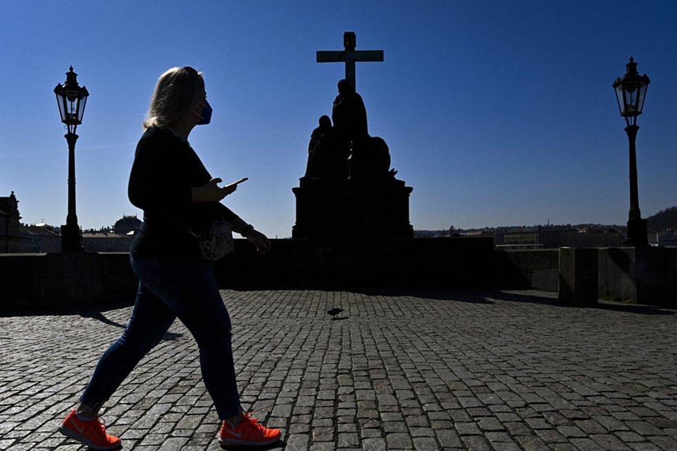 Žena s respirátorem prochází 31. března 2021 po téměř liduprázdném Karlově mostě v Praze