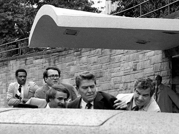 Americký prezident Ronald Reagan (uprostřed) je svými osobními strážci tlačen do limuzíny po atentátu, který na něj spáchal před washingtonským hotelem Hilton John Hinckley.
