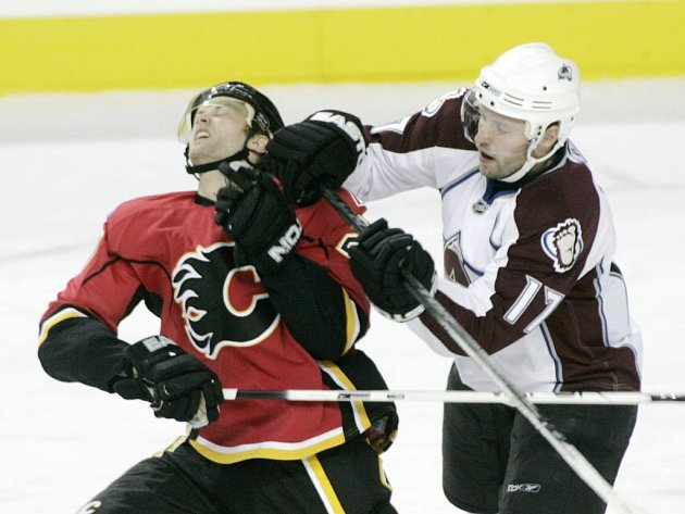 Jaroslav Hlinka z Colorada (vpravo) atakuje Kristiana Huseliuse z Calgary v průběhu vzájemného utkání.