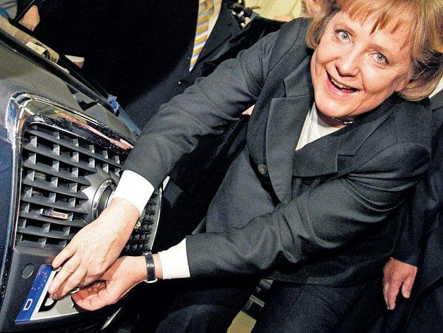 Německá kancléřka Angela Merkelová upevňuje na vozidlo nálepku, že prošlo emisními testy. Vyzkoušela si to při letošní návštěvě automobilového učiliště ve Frankfurtu nad Mohanem.