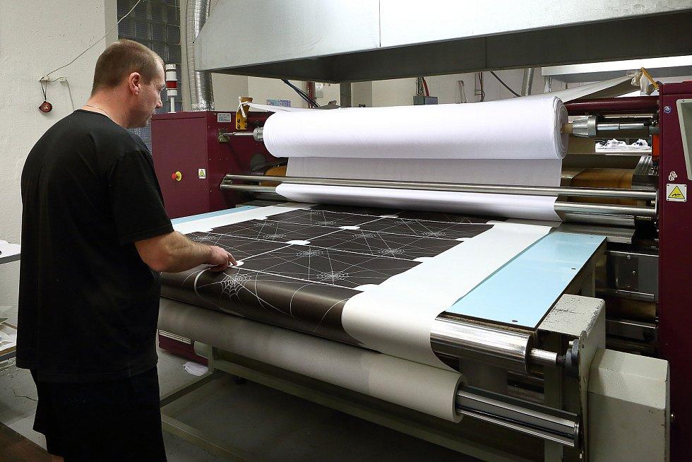 Potištěné role na podkladovém papírovém nosiči se vkládají do termosublimačního stroje. Tam se vzor i barva přenese na textilii, ze které se ušijí šátky či roušky.
