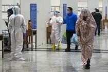 Zdravotníci v ochranných oblecích pomáhají pacientům nakaženým koronavirem v nemocnici přebudované z výstavnho centra ve Wu-chanu