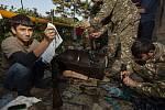 Mladí dobrovolníci pomáhají vojákům čistit zbraně konzervačním mazivem poblíž Hadrutu v Náhorním Karabachu