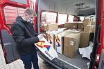 Ministr zahraničí Tomáš Petříček označuje nálepkami s českou a španělskou vlajkou krabice s humanitární pomocí České republiky, které 29. března 2020 odvážely kamiony z policejního skladu v Opočínku u Pardubic.