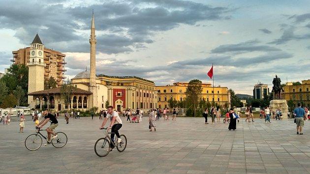 Skanderbegovo náměstí ilustruje albánskou historii. V pozadí domy postavené Mussolinim za italské okupace doplňuje mešita z dob turecké nadvlády a pravoslavný chrám. V pozadí pak moderní výškové budovy. Socha Skanderbega vystřídala Hodžu, předtím Stalina.