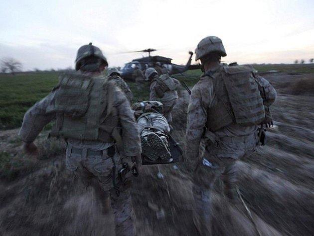 Američtí vojácí transportují během ofenzivy u afghánského Mardžáhu do vrtulníku jednoho ze zraněných po útoku na jejich vozidlo.
