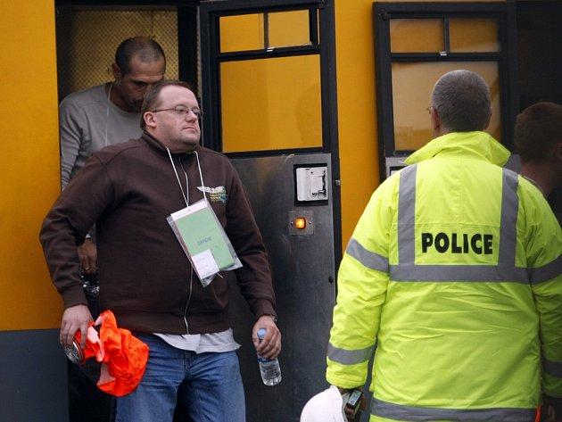 Řidiči kamionů vystupují ze záchranného vlaku, který je z hořícího tunelu dovezl do požární stanice ve francouzském Coquelles.