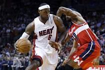 Hvězda Miami LeBron James (vlevo) se prosazuje přes Cartiera Martina z Washingtonu.