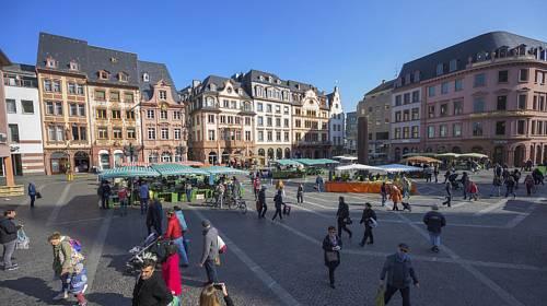 Zákazníci dodržují odstup na trhu na náměstí před katedrálou v Mohuči