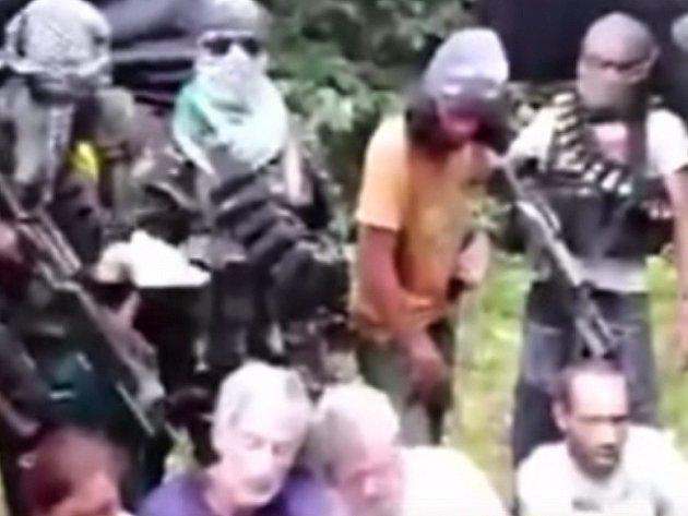 Rukojmí na videonahrávce sedí na trávě uprostřed džungle a jsou obklopeni více než desítkou většinou maskovaných ozbrojenců.