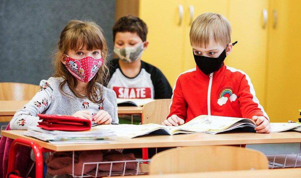Děti ve škole se musely učit i v rouškách.