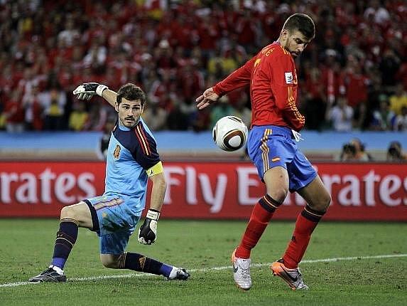Gólman Španělska Iker Casillas a Gerard Pique sledují míč, který míří do jejich sítě.