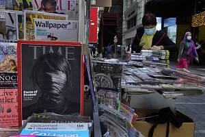 Prodejce tiskovin s rouškou v Hongkongu na snímku z 30. ledna 2020. Vpředu je časopis Time informující o čínském koronaviru