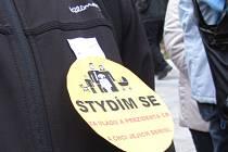 Protestující nosí žluté visačky s protestním sloganem