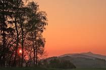 Západ slunce v pozadí se siluetou Ještědu.