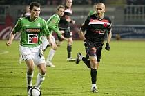 Baumit - Slavia 1:1. Na snímku domácí Luboš Loučka (vlevo v zeleno bílém) zakládá akci svého celku. Vpravo slávistický záložník Hocine Raqued.