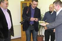 Jakub Faige (uprostřed) a ředitel archivu Jan Kašpar (vpravo) křtí knihu archivářským prachem