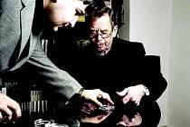 Václav Havel otiskává palec na leštěnou plochu medaile, na snímku s autorem Otakarem Duškem.