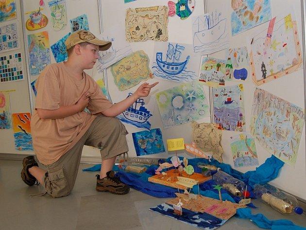 Andrej Výboch ze Základní školy Liberecká ukazuje své tři obrázky, které vystavuje na výstavě Plavu si – ani nevím jak.
