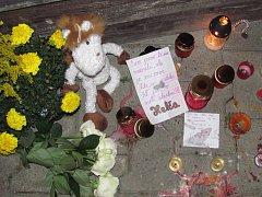 PŘED DOMEM, kde Johanka bydlela hoří svíčky, leží květiny. Kamarádi píší vzkazy.