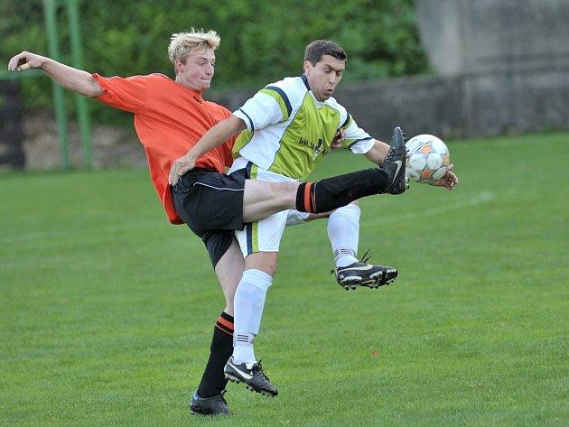V dalším utkání 1B. třídy se střetli hráči Sokola Plavy A s Malou Skálou A. Domácí obránce Jakub Černý  (vlevo v oranžovém) odvrací míč před hostujícím útočníkem Milanem Makulou (vpravo).