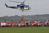 """HASIČI SI PĚKNĚ """"MÁKLI."""" Na čtvrtečním cvičení si jak profesionální, tak dobrovolní hasiči vyzkoušeli, jaké je naplnit vak 800 litry vody a pak správně navigovat vrtulník, aby efektivně uhasil hořící cíl. Celé akce se zúčastnilo více než sto lidí."""